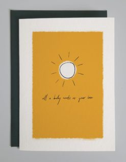 """Card design of a yellow box with a sketched sun and cursive writing that says, """"All a baby needs is your love"""""""