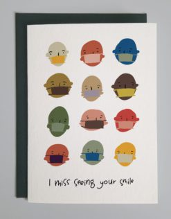 """Card with colorful faces wearing different colorful face masks over their noses and mouths. Words say """"I miss seeing your smile."""""""