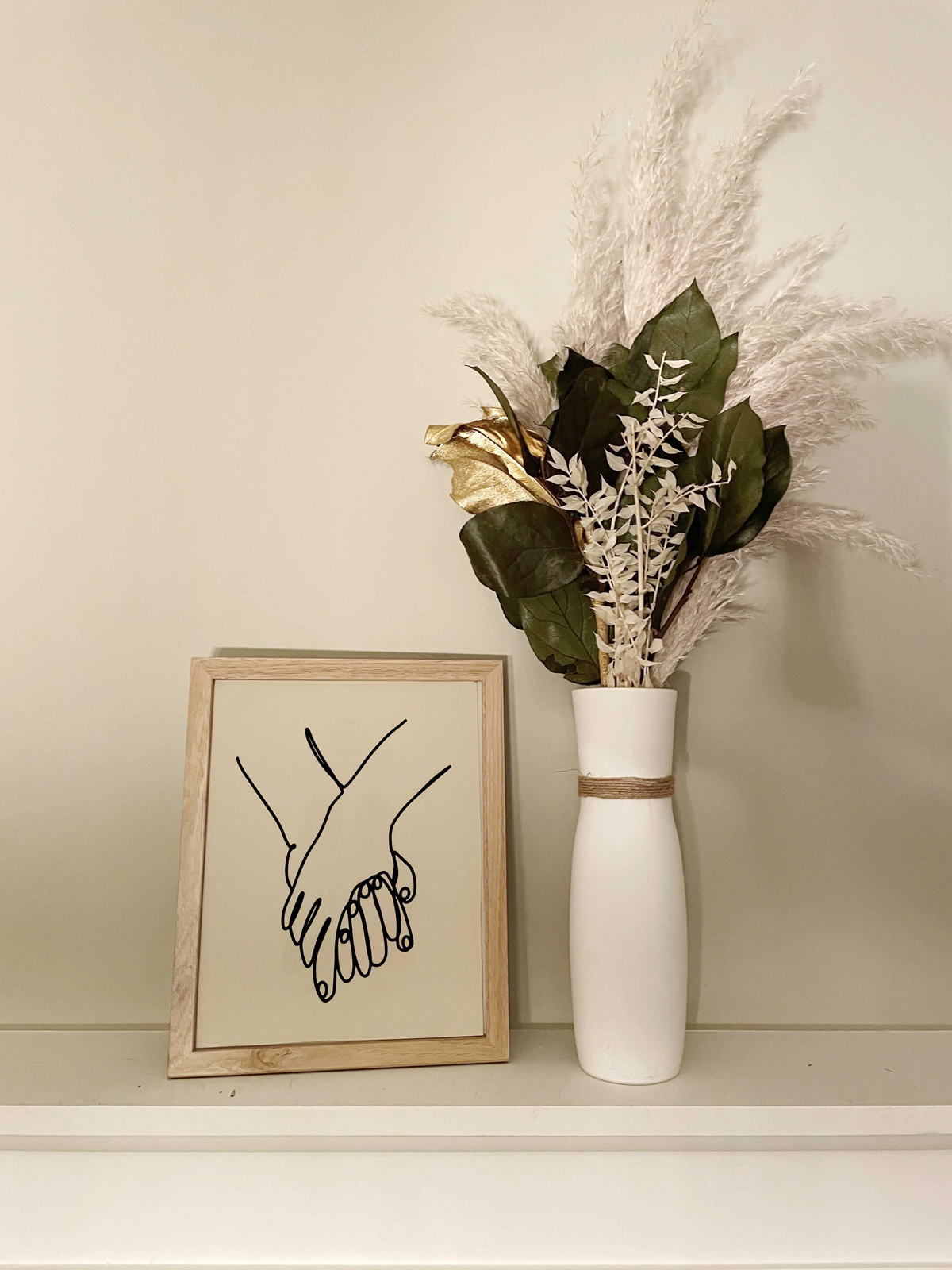 """Photo of """"Hands"""" art print in a frame next to flowers"""