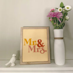 """Photo of """"mr and mrs"""" art print in a frame next to flowers"""