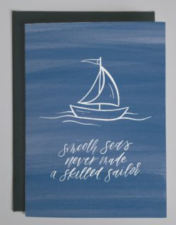 """Card with a blue painted background and a drawing of a sailboat with words that read """"smooth seas never made a skilled sailor"""" in script"""