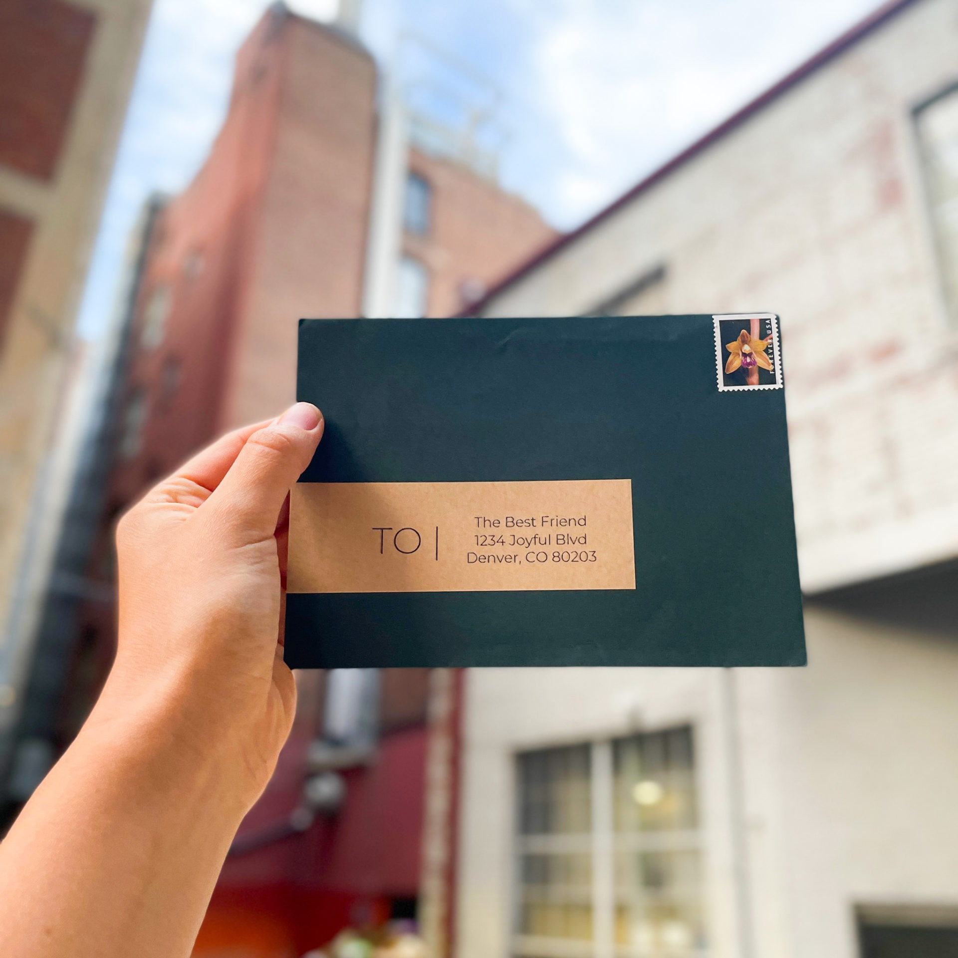 """image of a stamped, forest green envelope held up in front of blurry brick buildings. The envelope has a brown, kraft paper label that reads """"To"""" and an address"""