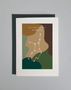 Image of a greeting card lying on top of a forest green envelope on a light gray background. Greeting card has an image of the constellation Virgo superimposed on a background of earth tones in geometric shapes. Card reads Happy Birthday Virgo