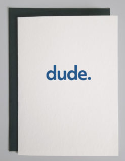"""Image shows a closed, white greeting card lying on top of a forest green envelope on a light gray background. The card reads """"dude."""" In blue."""